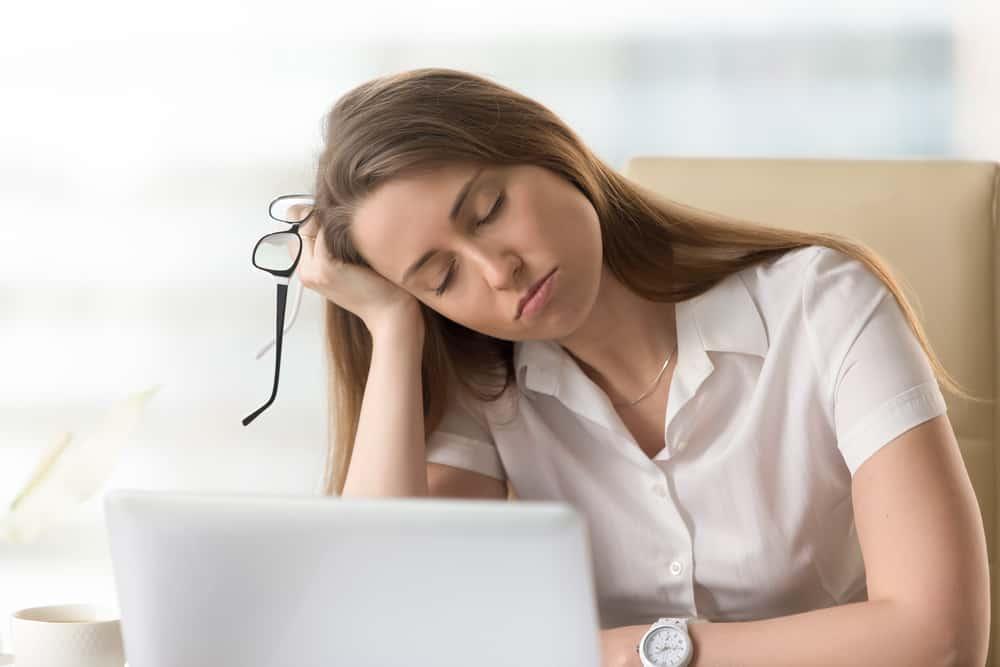 Bored sleepy businesswoman sitting half asleep at workplac