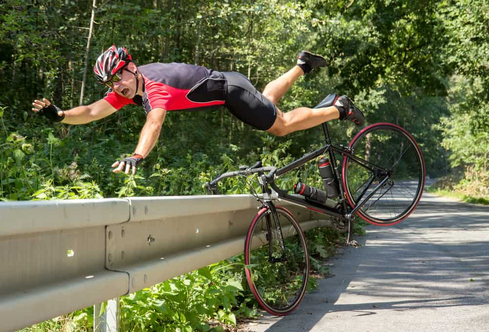 Cyclist falls off the bike into bushes. Accident on the road
