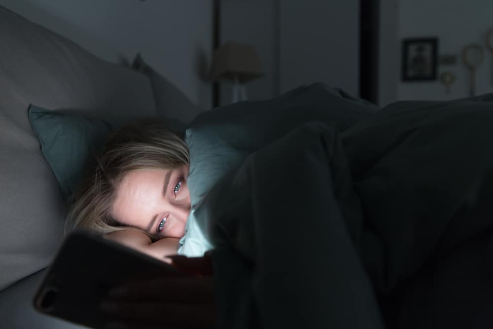 Portrait of young sleepy tired woman lying in bed under the blanket using smartphone at late night