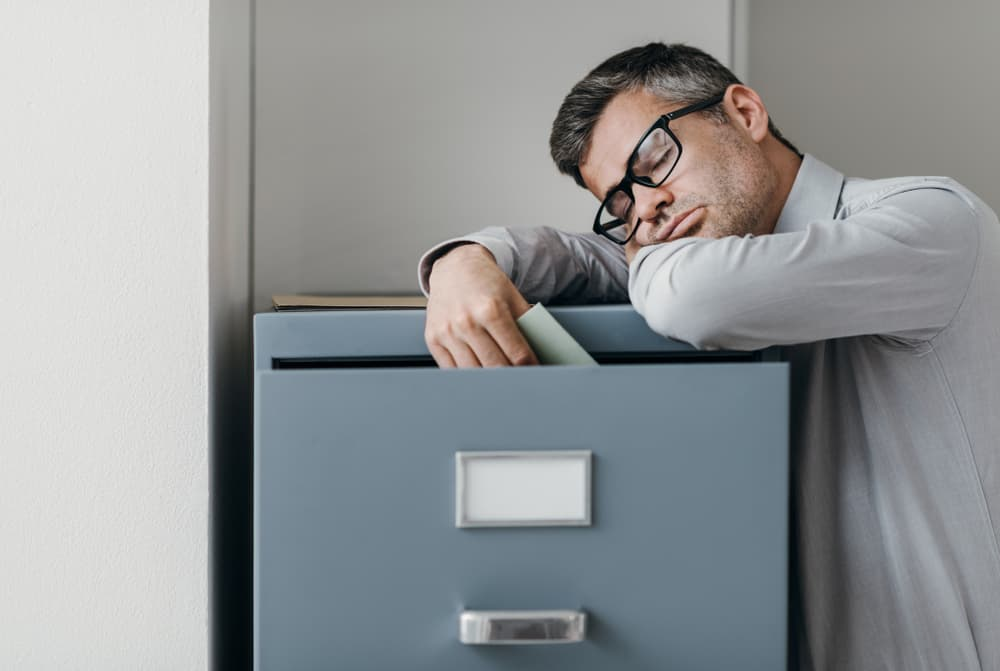 Tired lazy office worker leaning on a filing cabinet and sleeping