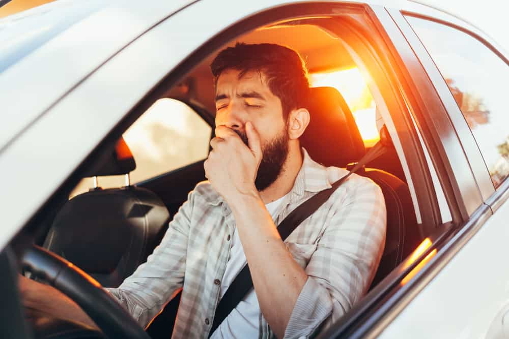Tired man yawning while driving his car